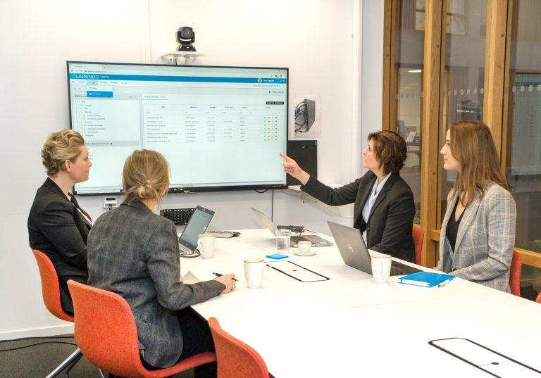 Kundmöte för implementering av ISO där ledningssystemet TIM visas på digital skärm